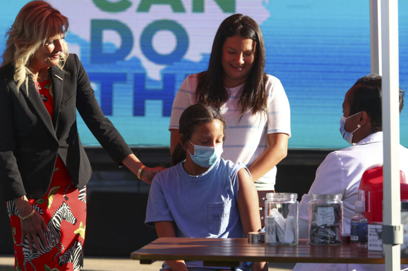 Grown women comfort a masked child with a rolled up sleeve.
