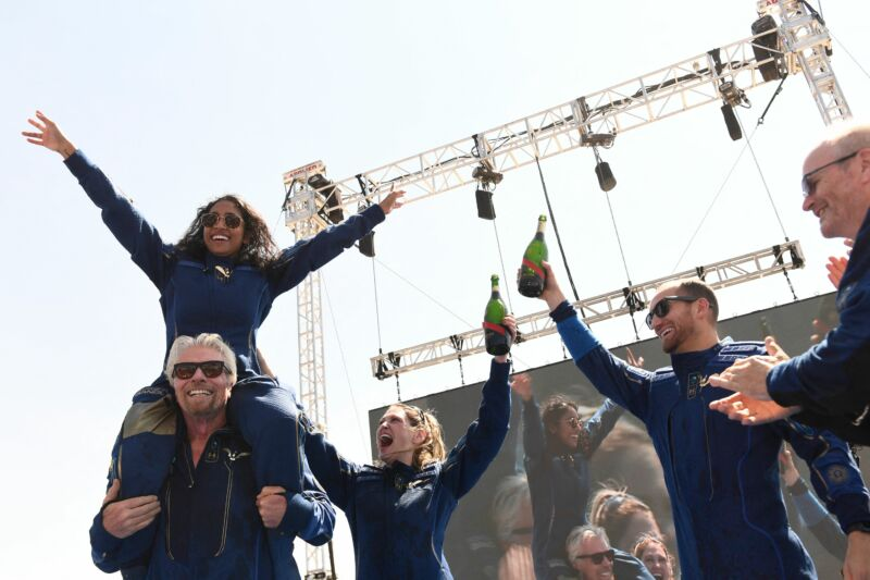 Virgin Galactic founder Sir Richard Branson, with Sirisha Bandla on his shoulders, cheers with crew members after flying into space aboard VSS <em>Unity</em>.