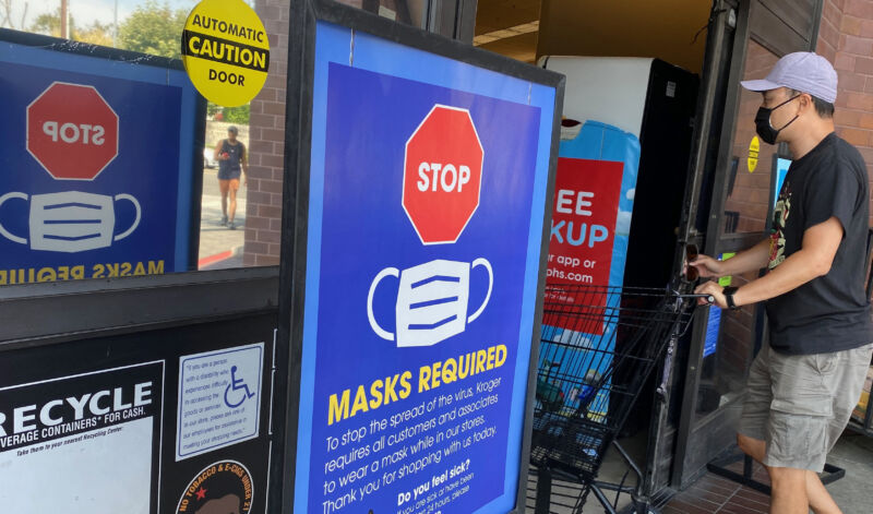 Signs requiring masks line the entrance to a grocery store.