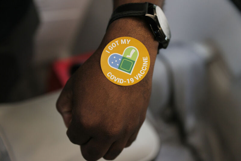 A person gets a sticker after getting a Pfizer-BioNTech COVID-19 vaccine.