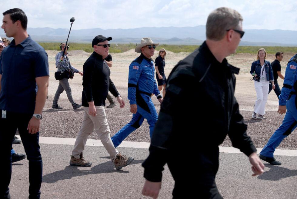 Blue Origin CEO Bob Smith (black hat) walks with Jeff Bezos after his flight on Blue Origin's New Shepard into space.