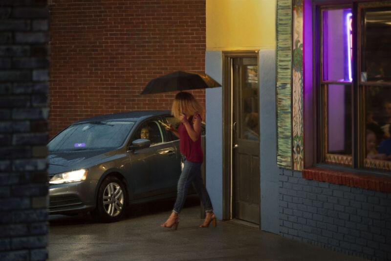 A woman in an umbrella walks to her Lyft.