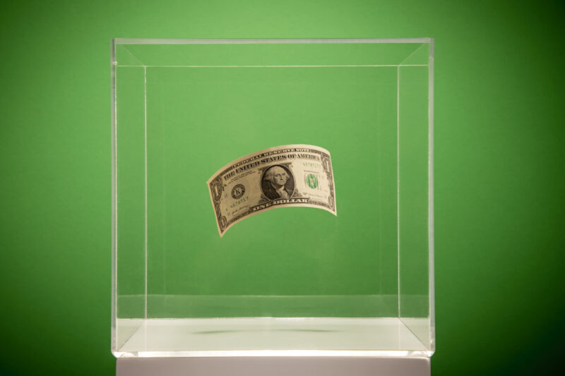 A dollar floats in a museum-style plastic display case.