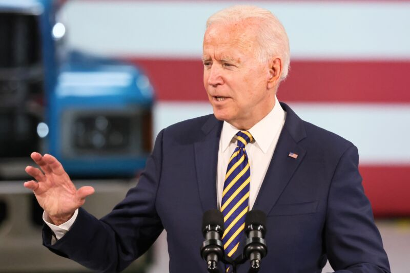 President Joe Biden speaking in front of a podium at a Mack Truck facility.