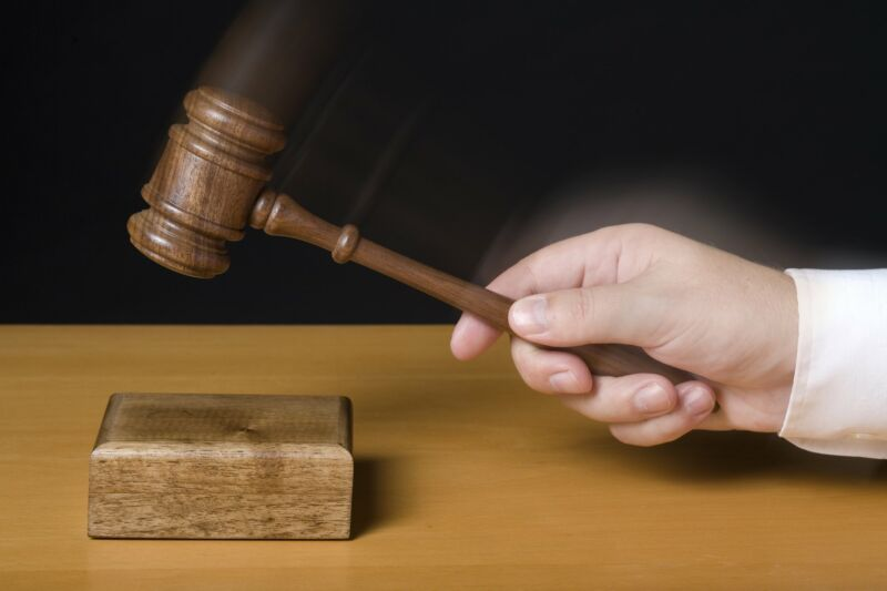 A judge's handing hitting a wooden block with a gavel.