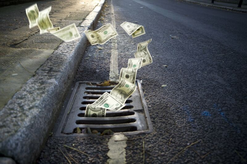 Money falling into a grate on the side of a street.