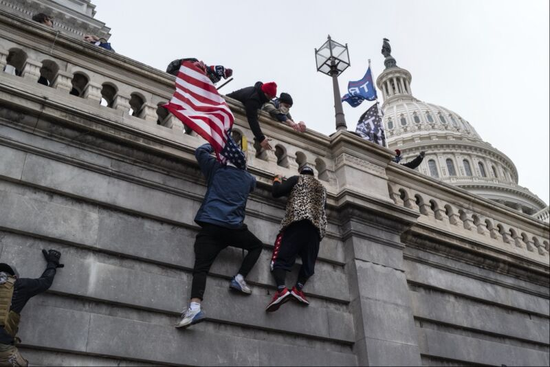 Trump supporters scaling the wall of the US Capitol building during the riot on January 6, 2021.