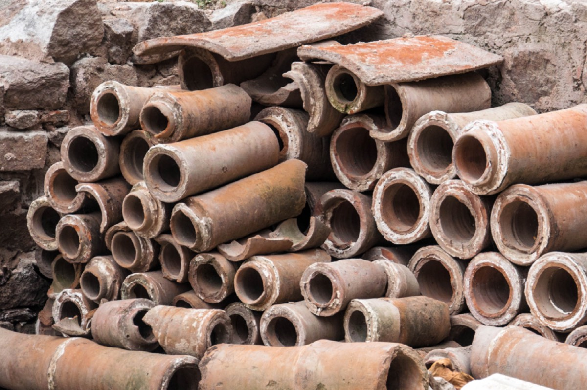 Ancient Roman sewer pipes stacked against a stone wall