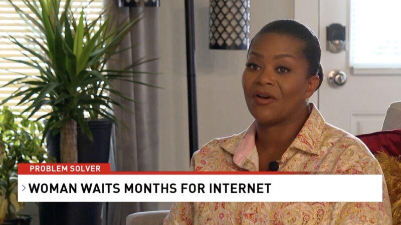 Una mujer sentada en su casa hablando con un reportero.  En la pantalla, el texto dice:
