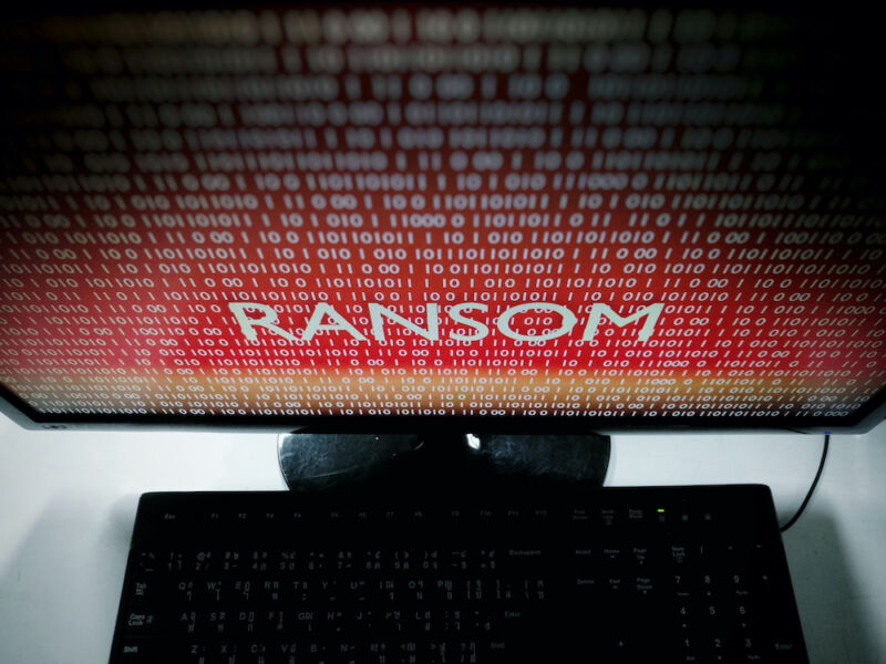 The word ransom dominates a menacing, red computer monitor.