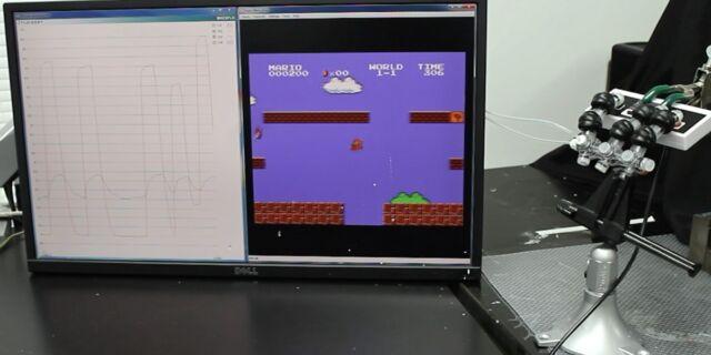 The soft robotic hand plays a round of <em>Super Mario Bros.</em>