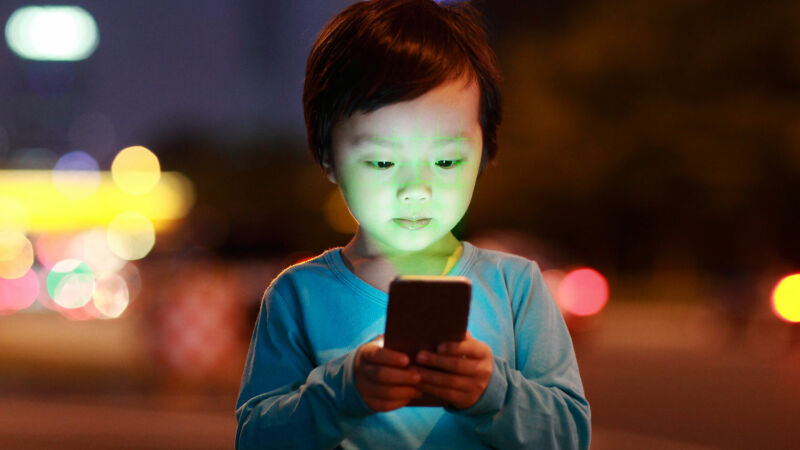 A child on streetside is fascinated by what is on a smartphone.