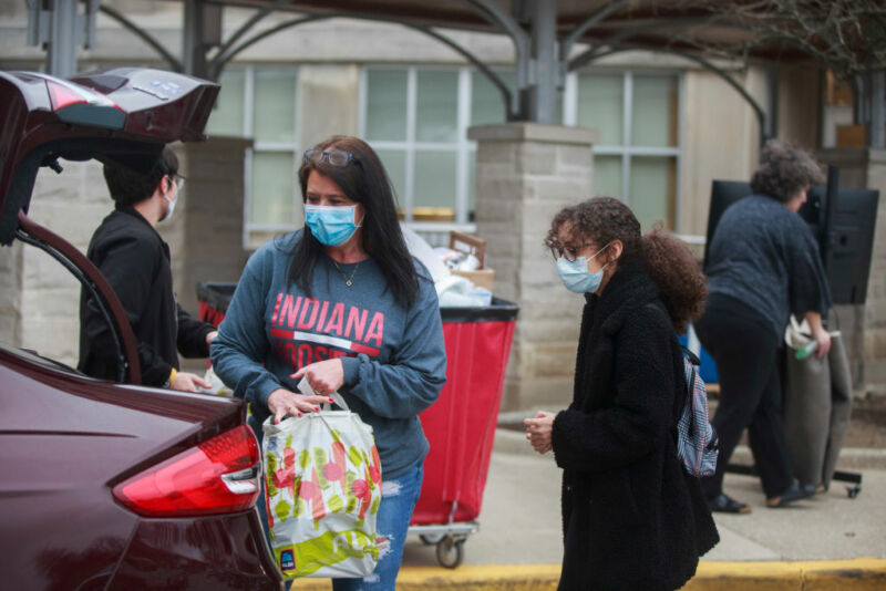 Image of masked parents and students near a car.