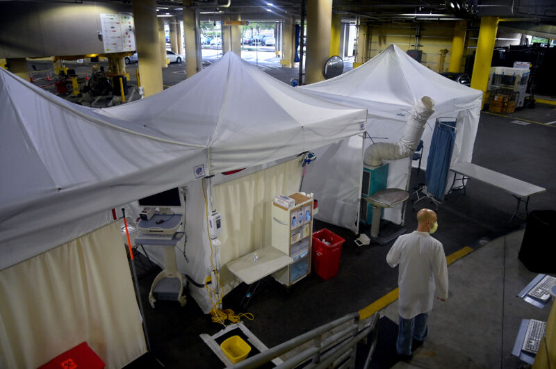 Emergency medicine specialist Dr. Davis Wein walks in a parking garage that was turned into a series of COVID-19 test tents at Tampa General Hospital in Tampa, Florida, on August 19, 2020.