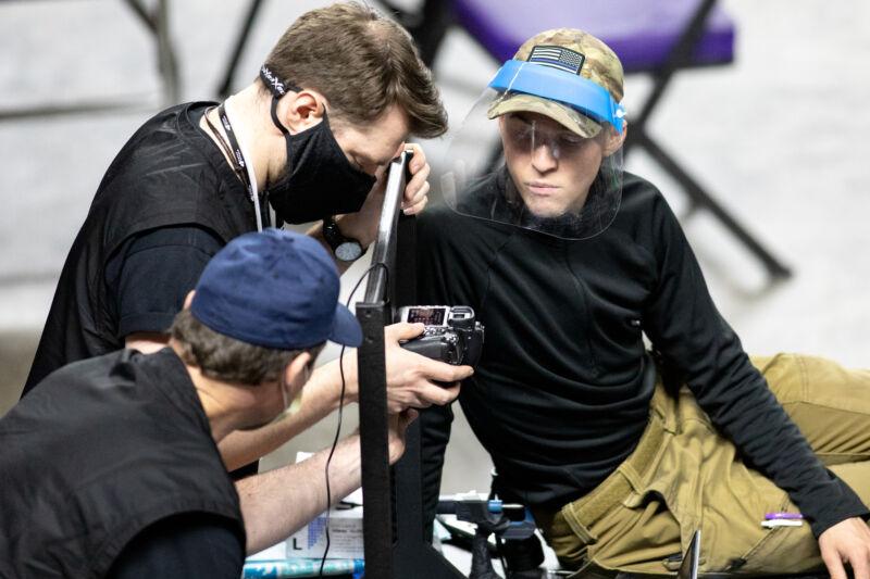 Men in face masks examine a digital camera.