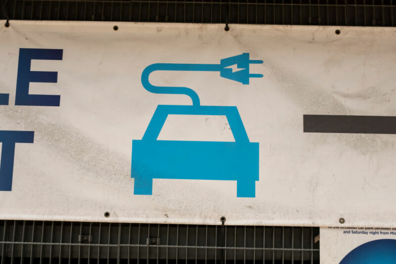 Outdoor signage advertises an electric vehicle charging station.