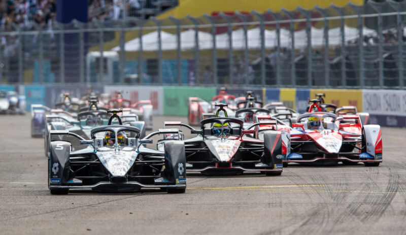 A group of Formula E cars race towards the camera