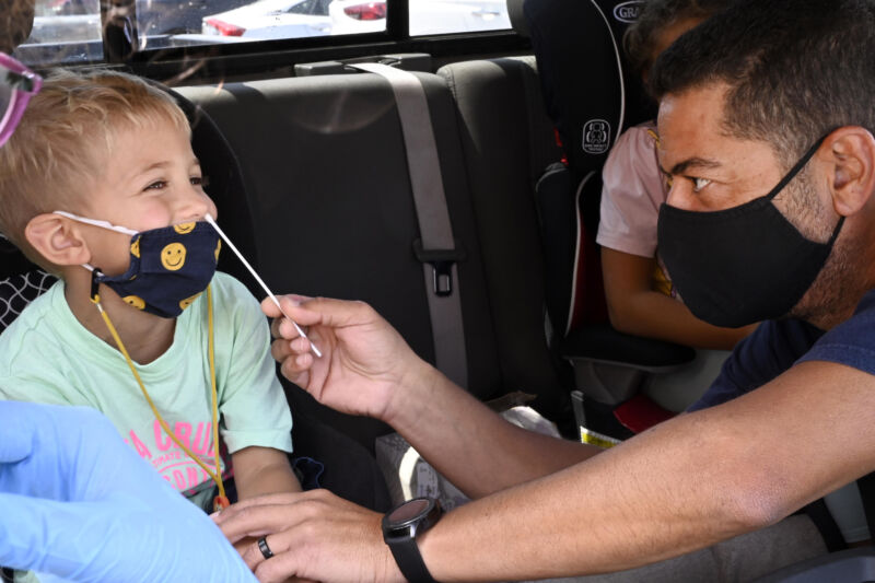 A kid gets a cotton swab shoved up his nose.