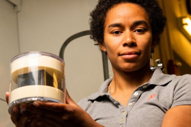 Brittany Robertson with PNNL's cube, which is in a protective case.
