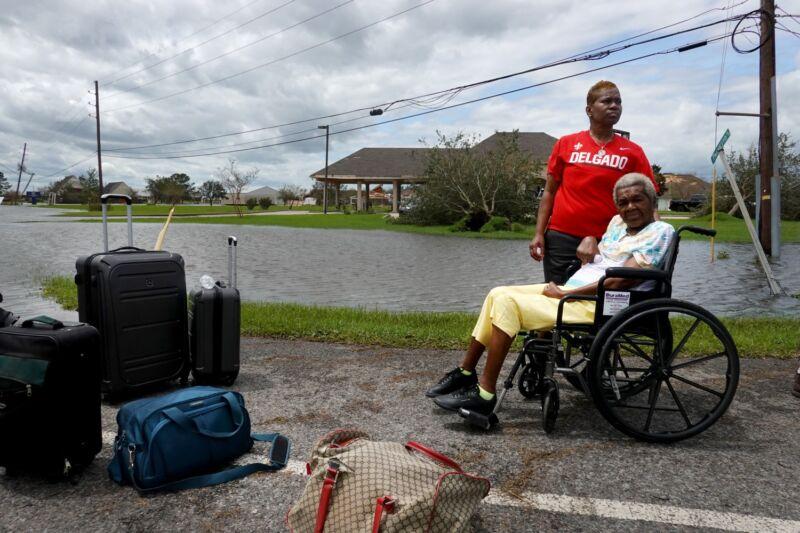 Una anciana en silla de ruedas y su hija esperando transporte en un barrio inundado.