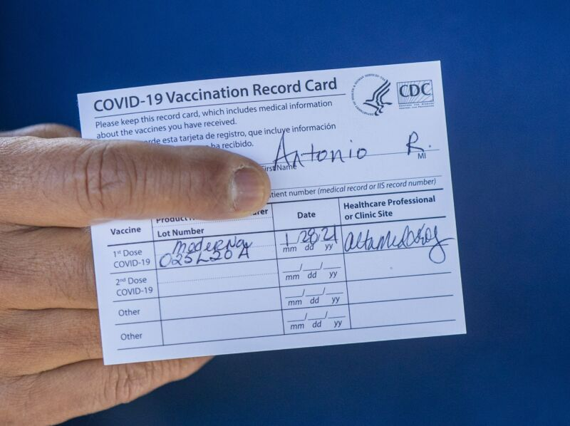 A man's hand holding a COVID vaccination card.