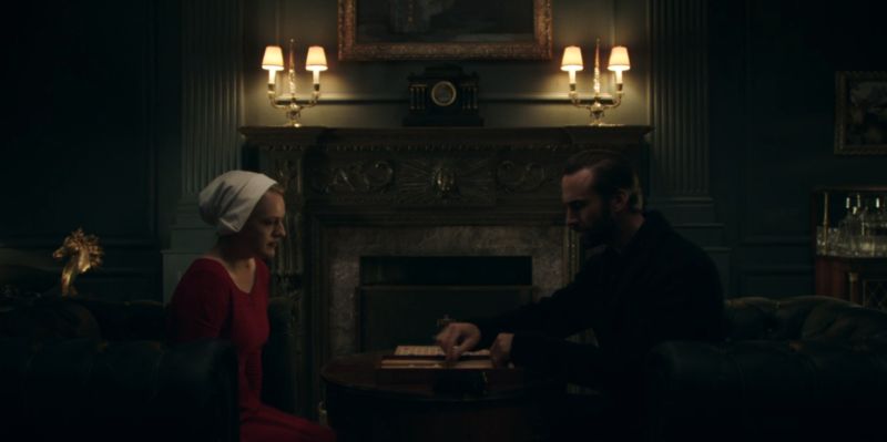 A man and a woman converse in a dimly lit room.