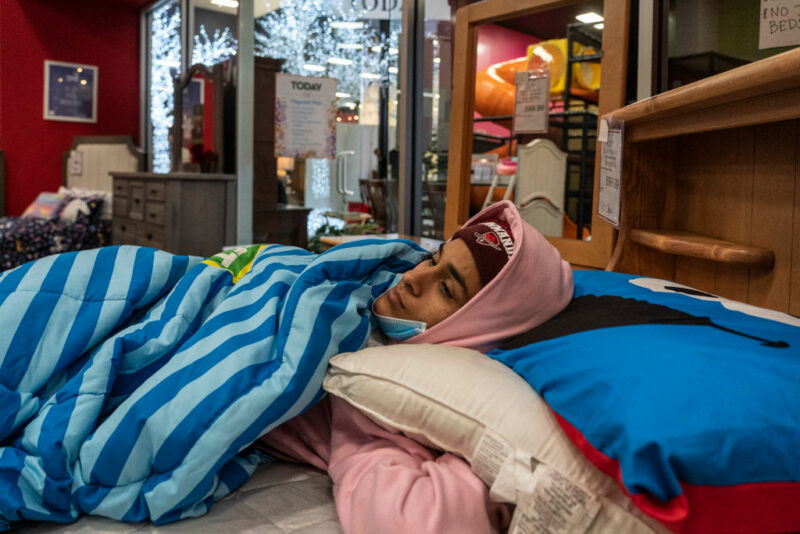 Image of a woman bundled against the cold on a bed in a furniture store.
