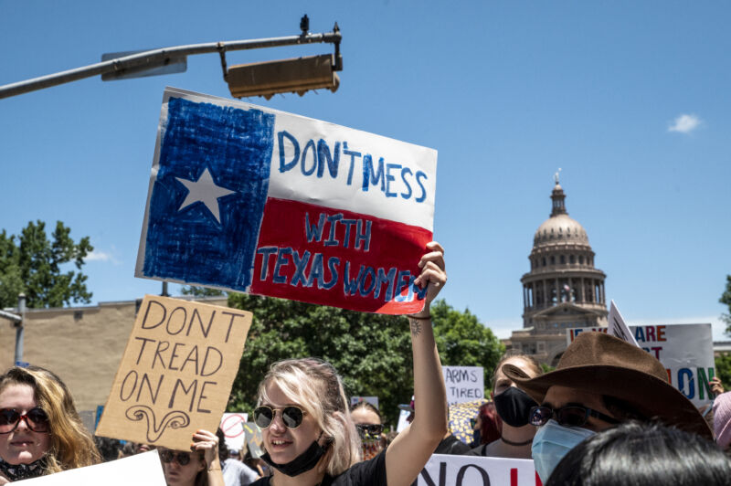 Protesters hold up signs as they march down Congress Ave at a protest outside the Texas state capitol on May 29, 2021 in Austin, Texas. Thousands of protesters came out in response to a new bill outlawing abortions after six weeks was signed into law by Texas Governor Greg Abbot.