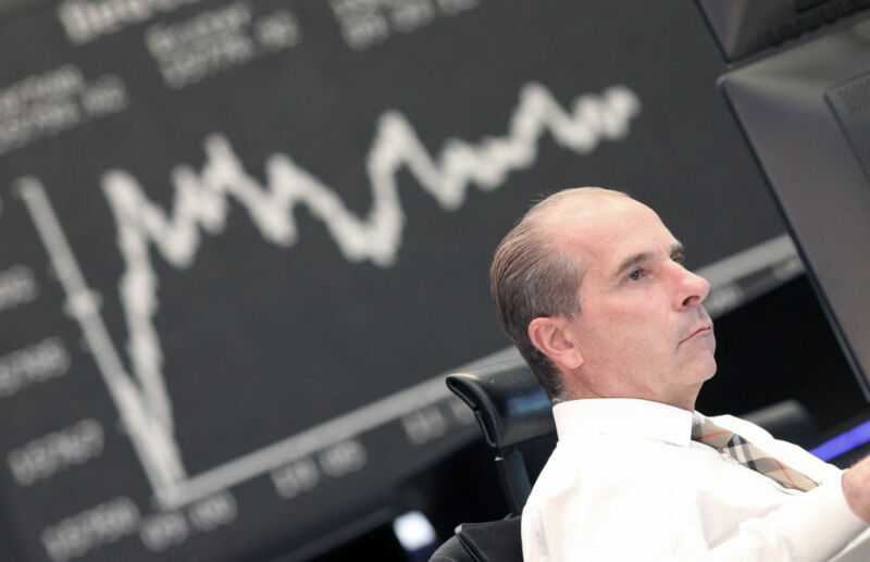 Image of a person in front of a graph tracking investment performance.