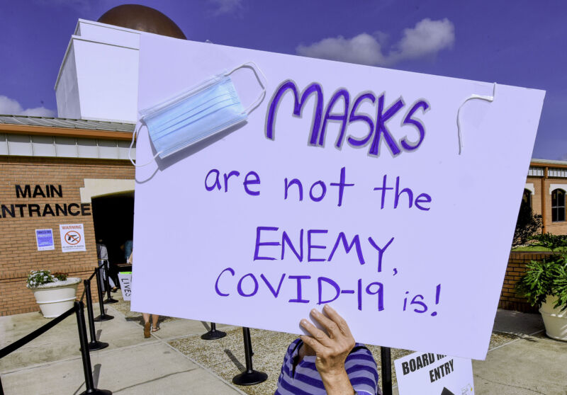 A protester holds a placard outside an emergency meeting of the Brevard County, Florida School Board in Viera to discuss whether face masks in local schools should be mandatory.
