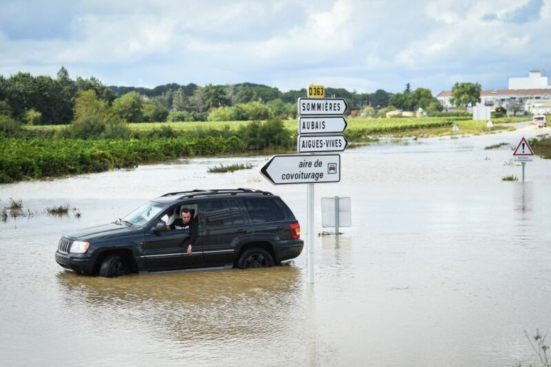 Image of a car stuck near a flooded road.