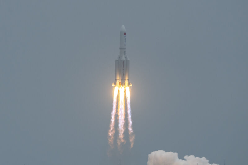 An ascending rocket leaves flame and smoke in its wake.