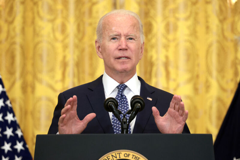 An older man in a suit speaks from a podium.