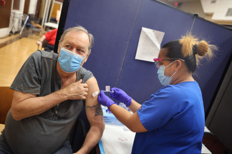 A health worker administers a COVID-19 booster vaccine and an influenza vaccine to an Army veteran at the Edward Hines Jr. VA Hospital on September 24, 2021, in Hines, Illinois.