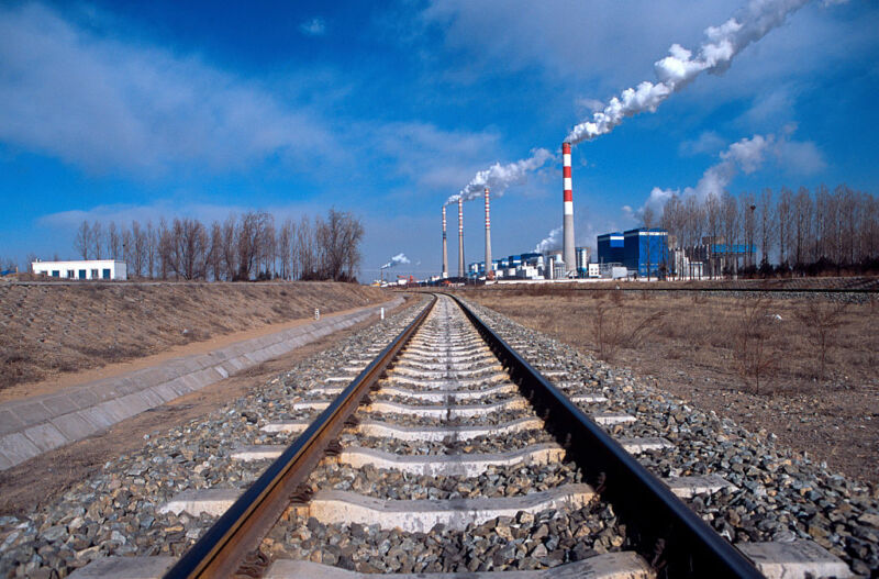 Image of railway tracks leading to a power plant.