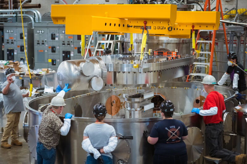 Image of a large metal oval being lowered into a tank by a crane as people observe.