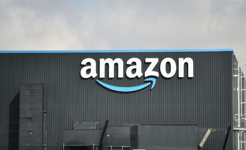 Outside view of a warehouse with a large Amazon logo on the side of the building.