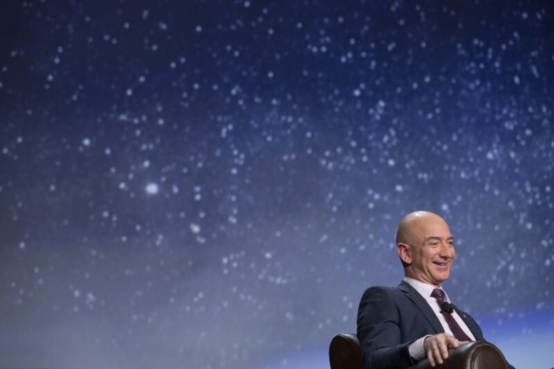 Jeff Bezos at a space conference, sitting in front of a picture of the stars in the night sky.