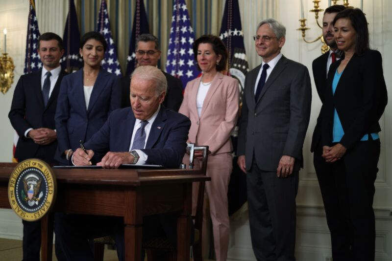 Joe Biden signs an executive order surrounded by various administration officials, including FCC Acting Chairwoman Jessica Rosenworcel.
