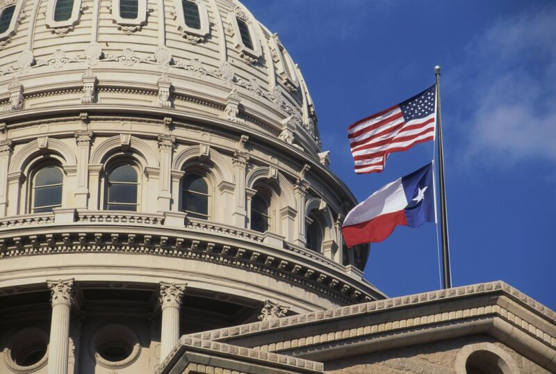 US and Texas flags in front of the Texas state capitol building.