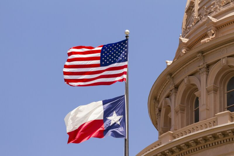 US and Texas flags seen in daytime outside the Texas State Capitol Building.