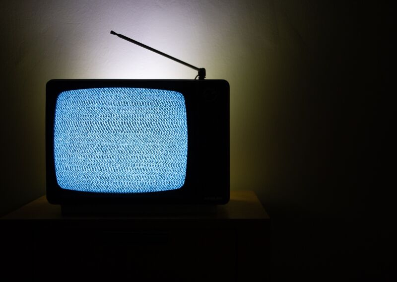 An old television with an antenna displaying static.