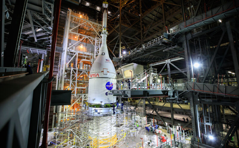 The Orion spacecraft for NASA's Artemis I mission is lifted above the Space Launch System rocket in the Vehicle Assembly Building at Kennedy Space Center.