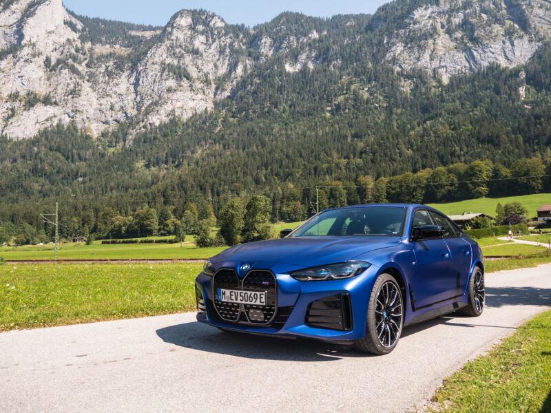 A blue BMW i4 next to some mountains