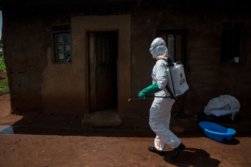 A woman in heavy protective gear walks outside a small house.