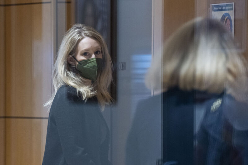 Elizabeth Holmes, founder of Theranos Inc., left, arrives at federal court in San Jose, Calif., on Tuesday, Oct. 12, 2021.