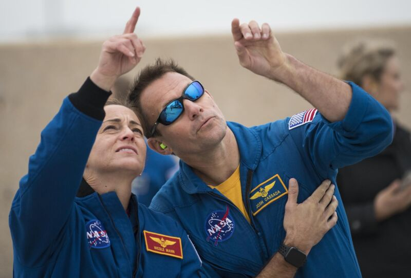 NASA astronauts Nicole Mann and Josh Cassada watch as an Atlas V rocket with Boeing's CST-100 Starliner spacecraft onboard is rolled to the launch pad ahead of the Orbital Flight Test mission in December 2019.