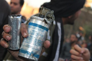 A protestor holds a used tear gas canister