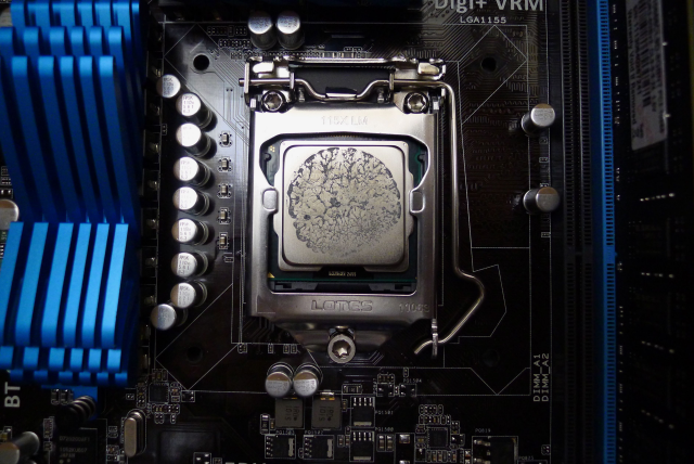 The CPU, in its socket with some thermal compound that's been transferred from the CPU cooler. Note the gold triangle lined up with the bottom left corner.