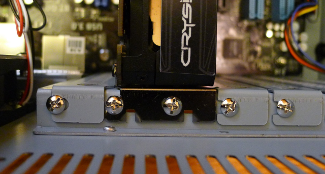 The side of the video card with ports is secured to the back of the case.